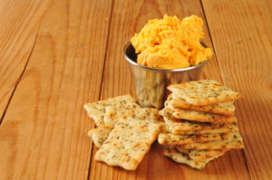 Italian herb flatbread crackers with bacon cheddar cheese spread on a rustic wooden surface