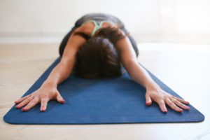 Woman doing stretching exercise on yoga mat. Fitness female performing yoga on exercise mat at gym. Child Pose Balasana.